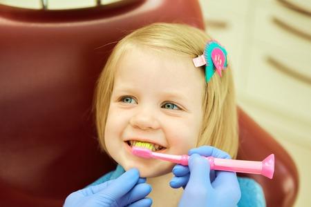 歯科医のオフィスに座っている小さな女の子。歯医者ブラシ歯の小さな女の子