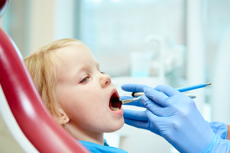 pediatric: Pediatric dentist examining little girls teeth in the dentists chair at the dental clinic Stock Photo