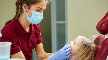 Pediatric dentist examining little girls teeth in the dentists chair at the dental clinic Stockfoto