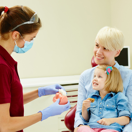 Pediatric dentist explaining to young patient and her mother the model in dental clinic Archivio Fotografico