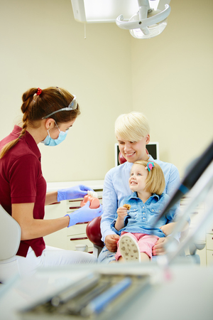 pediatric: Pediatric dentist explaining to young patient and her mother the model in dental clinic Stock Photo