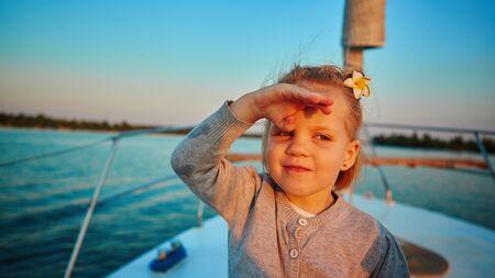 onboard: Little girl enjoying ride on yacht at sunset