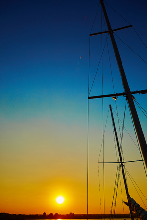 deportes nauticos: Sail boat gliding in open sea at sunset Foto de archivo