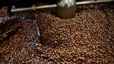 Roaster: Freshly roasted coffee beans in a coffee roaster. Shallow dof