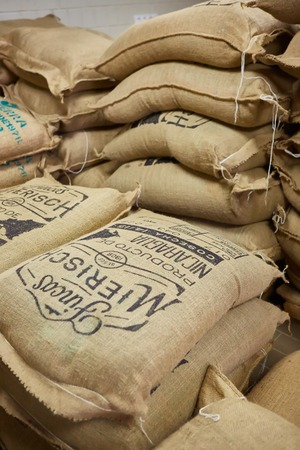 stack of burlap sacks with coffee beans at warehouse