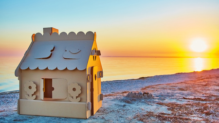 single family house: Toy house made of corrugated cardboard in the sea coast at sunset. The concept of eco-estate Stock Photo