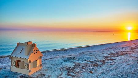 Spielzeughaus aus Wellkarton in der Küste bei Sonnenuntergang. Das Konzept der Öko-Siedlung