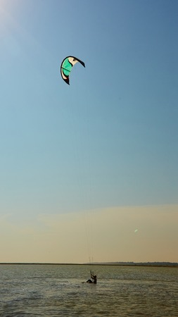 kiter: A young woman kite-surfer rides in summer day