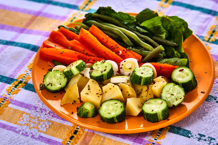 accompaniment: Ladle of steamed freshly harvested young vegetables including crinkle cut sliced carrots, peas and potato batons for a healthy accompaniment to dinner Stock Photo