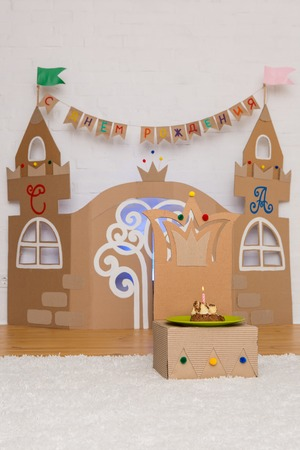 childish: cardboard childrens palace with a throne and a cake