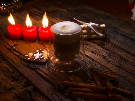 three layered: Frothy, layered cappuccino in a clear glass mug. Three red candles, cinnamon sticks and sweets. Romantic concept Stock Photo