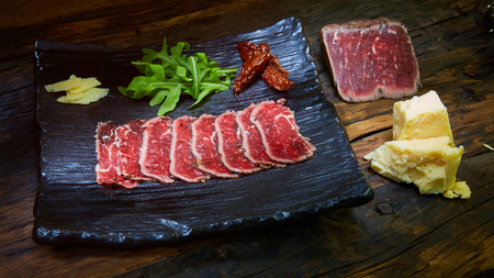 Sliced grilled meat with cheese and arugula on wooden background. Sous Vide