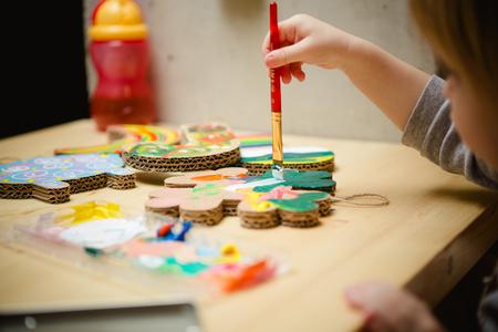 maquillaje infantil: Pequeña pintura bebé femenino con pinturas de colores. enfoque selectivo Foto de archivo