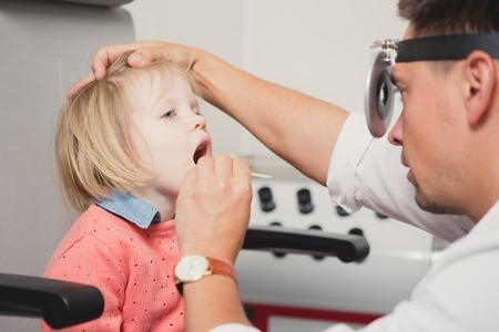 Arzt HNO-Überprüfung Ohr mit Otoskop zu Mädchen Patienten im Krankenhaus Standard-Bild