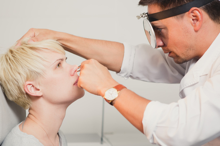 human nose: Doctor ENT checking ear with otoscope to woman patient at hospital Stock Photo