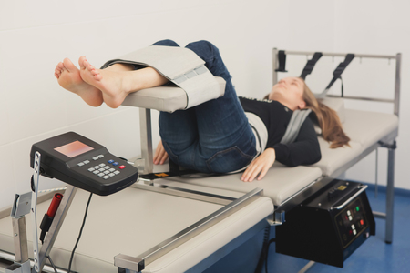 Spinal rehabilitation exercise on young woman. Spinal Decompression Therapy Archivio Fotografico