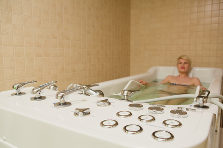 hydromassage: A woman and a hydro massage. She receives medical treatments for relaxation.
