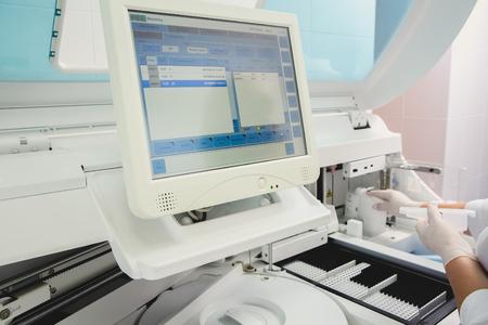 analyzer: Lab tech loading samples into a chemistry analyzer in clinic