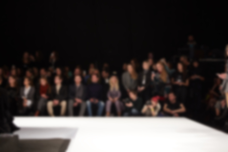 blurred image of group of audience at fashion show stage