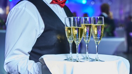 Waiter serving champagne on a tray at party Stok Fotoğraf