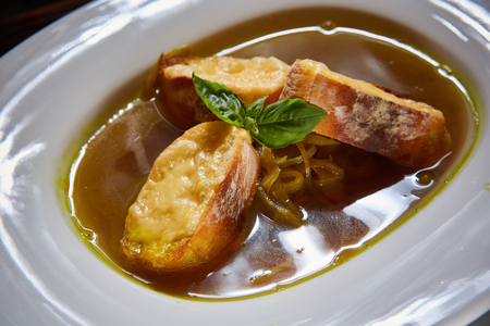 Bowl of tradiitonal French onion soup, with crusty bread and melting cheese