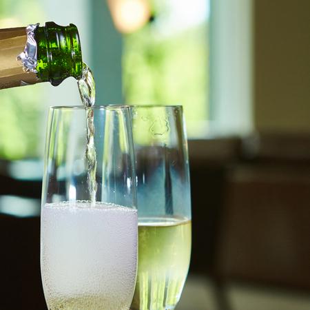 2 つのエレガントなグラスに注ぐシャンパン。クローズ アップ