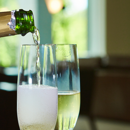 Champagne pouring in two elegant glasses. Closeup