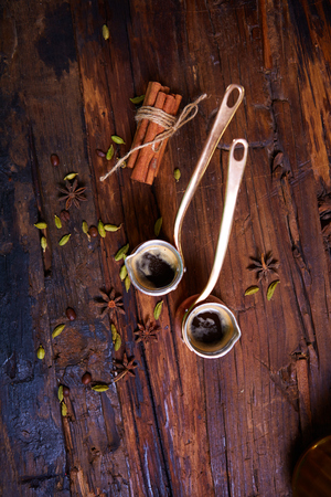greek pot: two Turk coffee on a wooden background with spices Archivio Fotografico