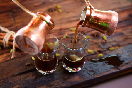 arabic coffee: To pour arabic coffee in cups on wooden background. Glass cups Stock Photo
