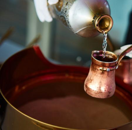 カフェバーで砂で cezve にトルコ コーヒーの調製 写真素材