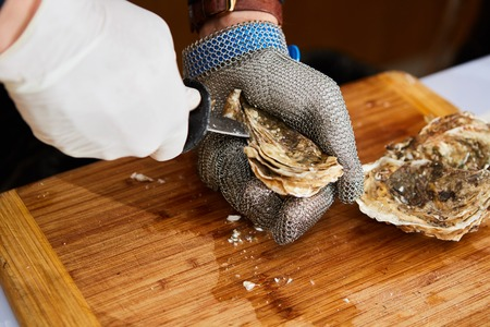 Fresh oyster held open with a oyster knife in a hand with an oyster glove Stock Photo