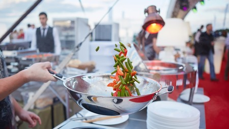 chef tossing vegetables in a wok in an outdoor kitchen