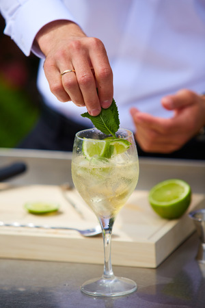 alcoholic drink: Bartender in nature preparing alcoholic drink mojito Stock Photo