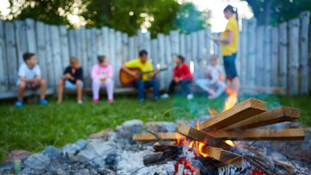 happy kids having fun around camp fire.