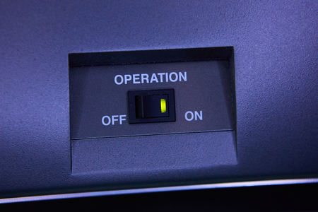 toggle switch: Black toggle switch on blue surface - on off.