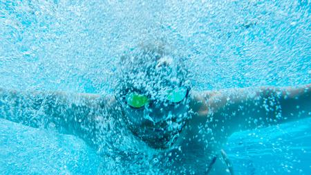 El nadador masculino bajo el agua en piscina del hotel