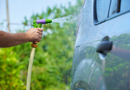 People cleaning car using high pressure water.