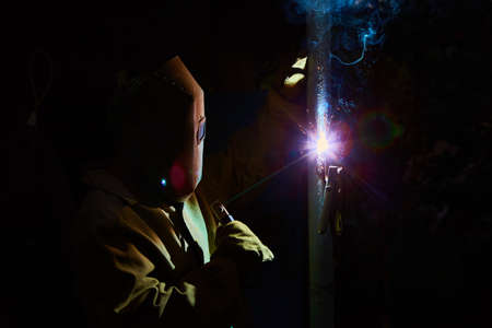 skilled labour: welder worker welding metal by electrode with bright electric arc and sparks during manufacture of metal equipment Stock Photo
