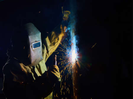 prefabricate: welder worker welding metal by electrode with bright electric arc and sparks during manufacture of metal equipment Stock Photo