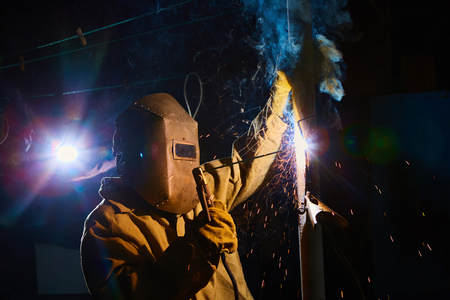 erecting: welder worker welding metal by electrode with bright electric arc and sparks during manufacture of metal equipment Stock Photo