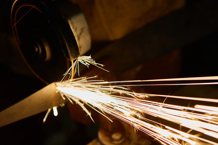 cutting metal: Worker cutting metal with grinder. Sparks while grinding iron.