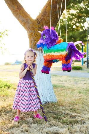 pinata: Young girl at an outdoor party hitting a pinata. Celebrating a birthday Stock Photo