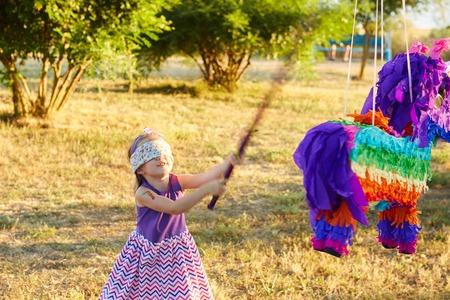 pinata: Young girl at an outdoor party hitting a pinata. Celebrating a birthday.
