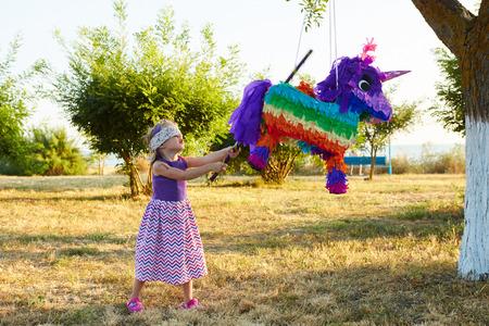 ピニャータを打つ屋外パーティーに若い女の子で。誕生日を祝っています。