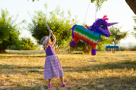 Young girl at an outdoor party hitting a pinata. Celebrating a birthday. Stock Photo