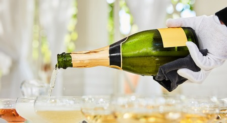 Pouring champagne in flutes standing on table.