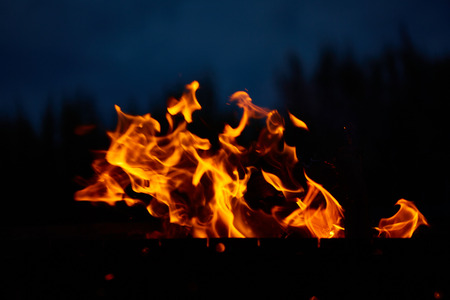 Close up shot of burning fire flame over ash inside of fireplace Stock Photo