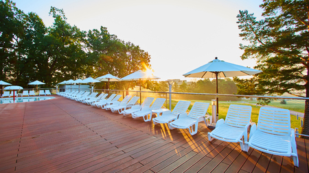 Relaxing chairs beside swimming pool Stock Photo