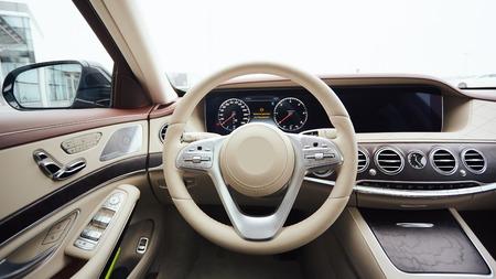 Lusso dell'automobile. Interno dell'auto moderna di prestigio. Sedili comodi in pelle, cruscotto e volante. Cabina di guida bianca con esclusiva decorazione in legno e metallo