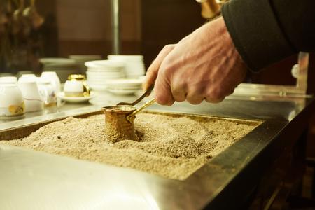 Schließen Sie herauf die Hände eines Mannes, der türkischen Kaffee auf heißem goldenem Sand kocht. Standard-Bild